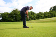 Putting for a Birdie. A junior golf champion putts in for a birdie stock photos