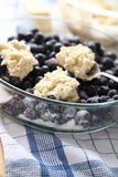 Putting biscuit topping on blueberry cobbler. Dropping biscuit dough onto sugared blueberries before baking royalty free stock images