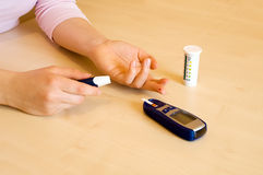 Putting blood drop. Putting a blood drop on test strip to measure glucose level royalty free stock image