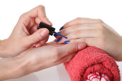 Putting blue nail lacquer Royalty Free Stock Image