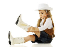Putting on the Boots. An adorable young cowgirl putting on her boots. On a white background stock photos