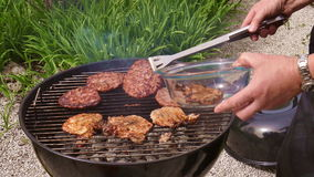 Putting Burgers And Steaks In A Gril stock footage