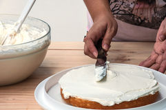 Putting butter cream cake by hand. Using spatula stock images