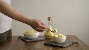 Putting butter into millet porridge stock footage