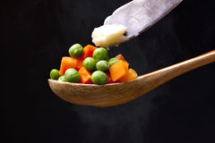 Putting butter on peas and carrots. Royalty Free Stock Photos