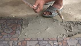 Putting ceramic tile on the floor stock footage