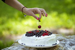 Putting cherry on the cake Royalty Free Stock Photo