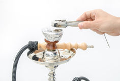 Putting coal on a hookah Royalty Free Stock Image