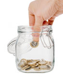 Putting coin into money jar isolated. Hand putting one euro coin into money jar isolated on white Stock Photos
