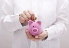 Putting coin into the piggy bank Royalty Free Stock Photos