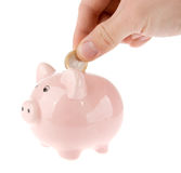 Putting coin into piggy bank isolated. Hand putting one euro coin into piggy bank isolated on white Stock Photo