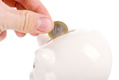 Putting coin into piggy bank isolated. Hand putting one euro coin into piggy bank isolated on white Royalty Free Stock Photos