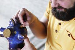 Putting a coin piggy bank Stock Photography