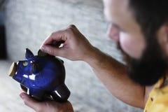 Putting a coin piggy bank Stock Photos