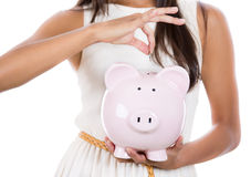Putting coin in piggy bank Royalty Free Stock Images
