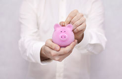 Putting coin into the piggy bank Stock Image