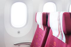 Putting coins into piggy Bank-The concept of savingsA row of seats and windows in an aircraft cabin royalty free stock images