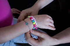 Putting colored beads bracelet on hand. Sophie name. Stock Photo