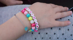 Putting colored beads bracelet on hand. Sophie name. Stock Images
