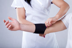 Putting on compression band. A doctor putting a compression band on a patients arm royalty free stock image