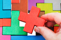 Putting cross shaped piece in wooden puzzle Stock Photo