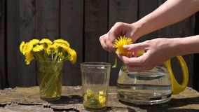 Putting a dandelion into a glass. In slow motion. Shot outdoors at noon stock video footage