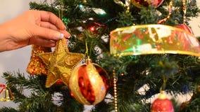 Putting decoartion on Christmas tree, closeup stock footage
