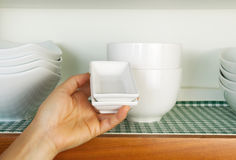 Putting Dishes back into Cabinet Royalty Free Stock Photography