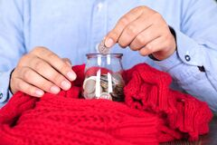 Putting dollar coins into a glass bottle piggy bank wrapped in a red scarf