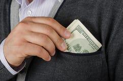 Putting dollar of pocket Stock Image