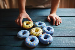 Putting donuts on table Stock Images