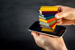 Putting or download colorful books to the smart phone with place Stock Photography