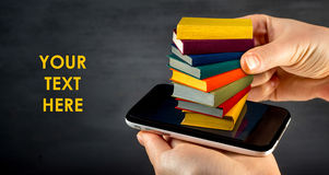 Putting or download colorful books to the smart phone with place. For your text royalty free stock images