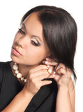 Putting on earings. A beautiful woman putting on pearl earings Stock Images