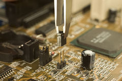 Putting electrical jumper on motherboard contacts. Expert is putting electrical jumper on motherboard contacts with miniature forceps to lock electrical circuit Stock Photography