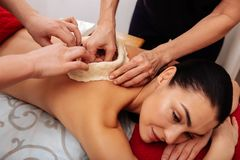 Experienced workers of SPA salon creating special construction. Putting equipment. Experienced workers of SPA salon creating special construction on client back stock images