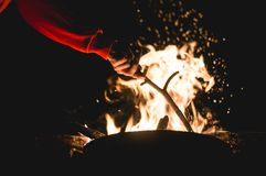 Putting extra wood on campfire Royalty Free Stock Images