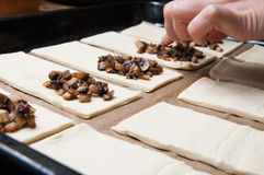 Putting fillings. Puff pastry tray with cheese and mushrooms fillings ready for baking royalty free stock image