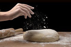 Putting flour on pizza dough. Stock Images