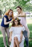 Putting a flower wreath to the hairs of young beautiful model. Royalty Free Stock Photos