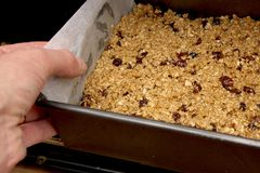 Putting fruit flapjack mix into the oven.  Stock Photos