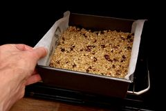 Putting fruit flapjack mix into the oven.  Royalty Free Stock Photo