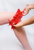 Putting a garter on the leg of a bride. Mother puts a red garter on the leg of her daughter Stock Images