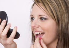 Putting on Gloss. A beautiful young woman puts on pink lip gloss Royalty Free Stock Photo