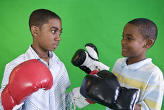 Putting on the Gloves. Two African American boys wearing boxing gloves as if ready to spar Stock Images