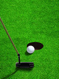 Putting Golf Ball Close to Hole With Copy Space. Golfer using a putter club to hit a relatively short and low-speed stroke on golf ball at short distance to hole Royalty Free Stock Photos