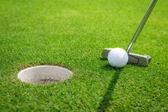 Putting a golf ball on the green Royalty Free Stock Photos