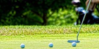 Putting golf ball into hole Stock Photo