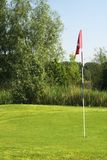 Putting green. Flag on pole, pin, at hole in putting green on golf course royalty free stock images
