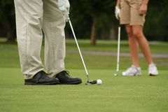 Putting green. Legs of golfers on the green. Shallow dof Royalty Free Stock Image